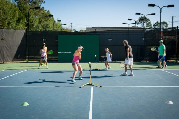Young players training tennis with Lenny Schloss