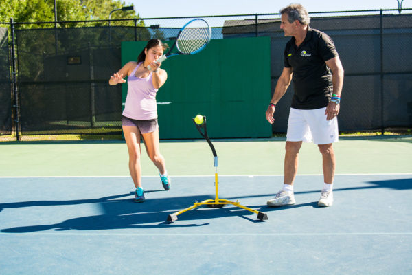 A woman training tennis Eye Couch Pro with coach