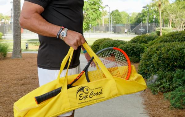 A man carrying a yellow Eye Coach tennis bag