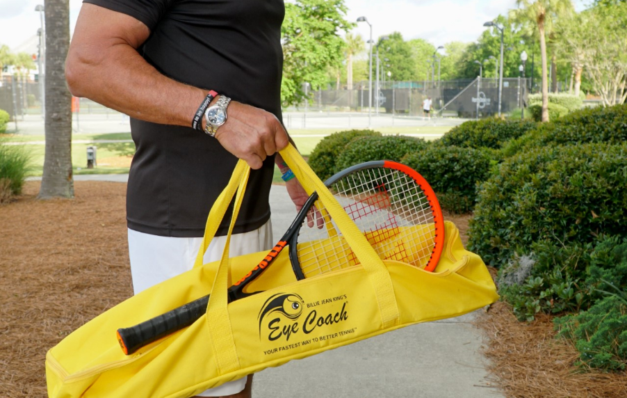 A man carrying a yellow Eye Coach tennis bag