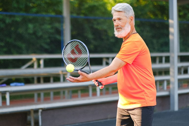 A man playing tennis during a sunny day