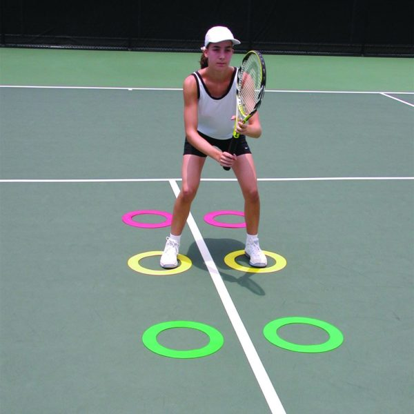 A woman training with Quick Feet Donuts on a tennis court